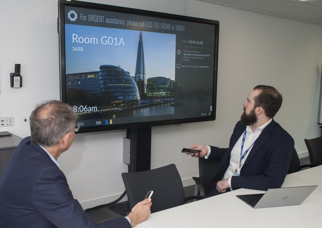 Two men in a meeting room collaborating with digital content on the screen in front of them.